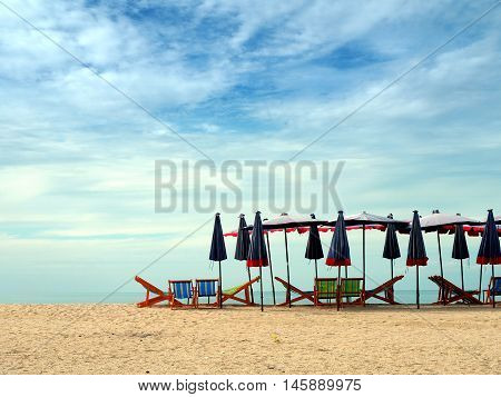 Colorful beach chairs and umbrellas with blue sky for tourism relax in vocation at Cha-Am beach Thailand