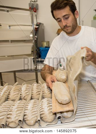 Baker putting unbaked bread dough into the hot oven in a bakery