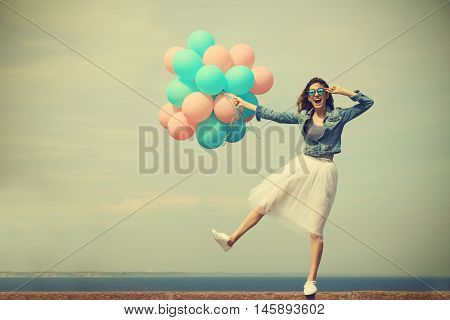 Beautiful young woman with colorful balloons on sea front