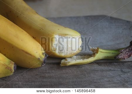 A banch of bananas and a sliced banana in a pot over a table.