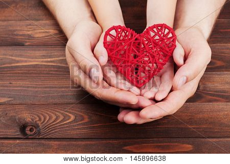 Adult and child holding red heart in hands over a wooden table. Family relationships health care pediatric cardiology concept.