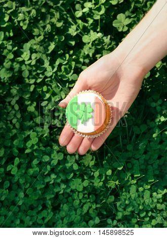 Woman holding tasty cupcake. Saint Patrics Day concept