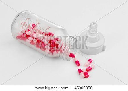 Feeding bottle with pills on white background