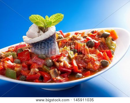 Tunisian salad with red peppers marinated fish and capers. Horizontal shot