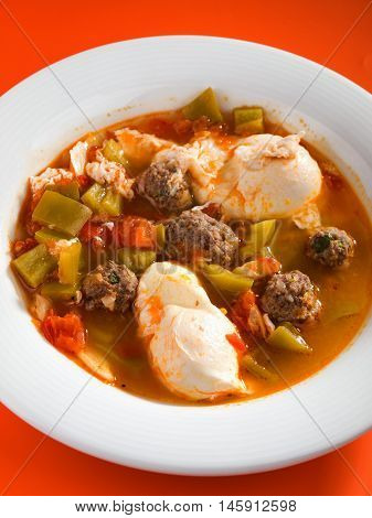 Tunisian soup with meatballs vegetables and poached eggs. Vertical shot