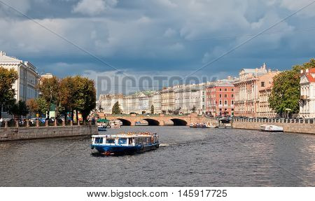 SAINT - PETERSBURG, RUSSIA - SEPTEMBER 5, 2016: People in the tourist boat sail on the Fontanka River. On the background is The Anichkov Bridge with The Horse Tamers by Peter Klodt near Nevsky Avenue