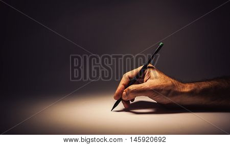 Conceptual composition about writing or drawing, male hand holding a graphite pen.