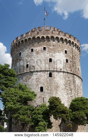 Thessaloniki, Greece. The White Tower with Greek flag waving on top. The White Tower is the landmark of Thessaloniki.