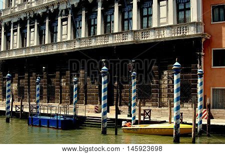 Venice Italy - June 10 2006: Blue and white striped boat mooring poles stand in the Grand Canal in front of a 16th century palazzo