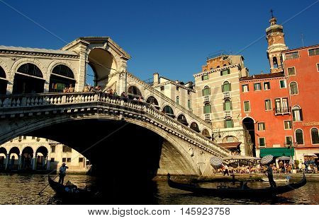 Venice Italy - June 11 2006: Gondolas pass under the famous Rialto Bridge (Ponte di Rialto) spanning the Grand Canal