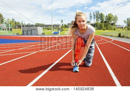 Portrait of confident woman tying sport shoe lace on running tracks