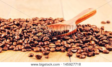 wooden spoon with coffee beans on table