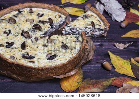 mushroom onion quiche on a dark wooden background. selective focus