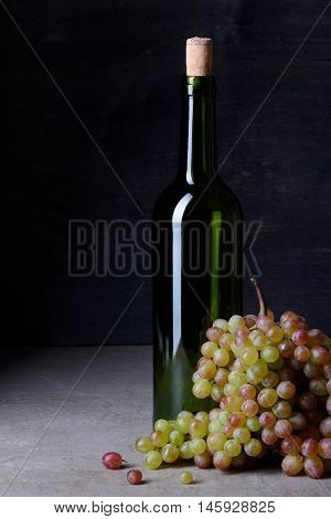 Bottle of wine with fresh ripe grapes. Sommelier background. Copy space, dark background.