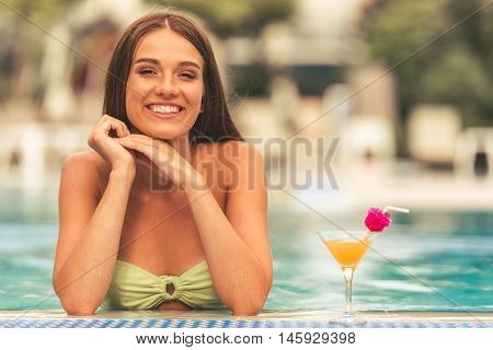 Pretty girl in green swimwear is drinking cocktail looking at camera and smiling while swimming in the pool