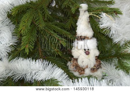 Christmas toy in the form of the gnome. The toy is located on a fir-tree. The gnome is made of fir cones and cotton