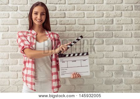 Attractive young girl in casual clothes is holding movie clappers looking at camera and smiling on white brick wall background