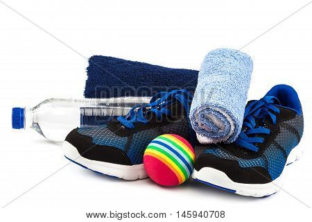 Sport shoes towels ball and water bottle isolated on a white background.