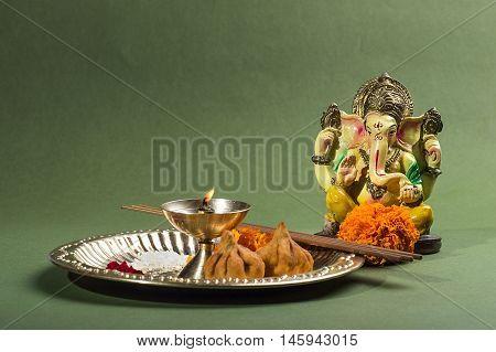 Hindu God Ganesha. Statue of Lord Ganesha. Pooja arrangement on green background.