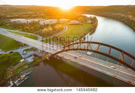 Sunset Sunrays Aerial Above Pennybacker Bridge or 360 Bridge or Capital of Texas highway Bridge Austin Texas cars driving across the Colorado River as Boat passing under the Suspension Bridge