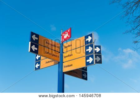 pole with lots of directional signs in a recreational area