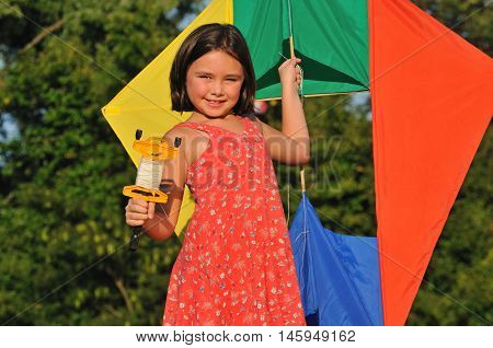 Cute kid launching a colorful kite out in the park
