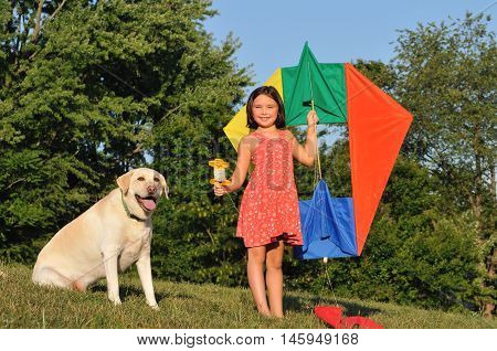 Happy girl launching a colorful kite in a grassy park