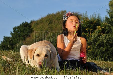 Young girl sitting on the grass with dog and blowing bubbles