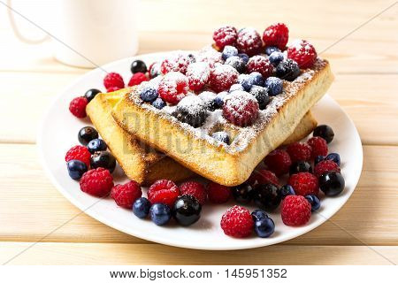 Breakfast waffles with fresh berries and coffee mug. Soft Belgian waffles with blueberry raspberry and blackcurrant.