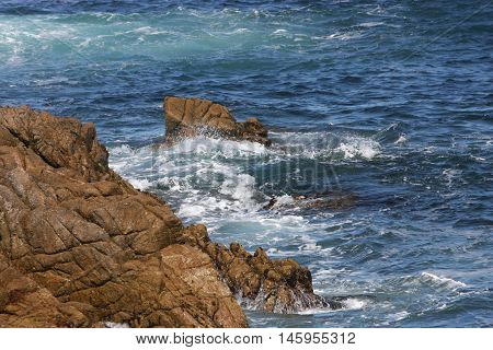 This is an image of rocks and the incoming tide at Asilomar State Preserve in Pacific Grove, California.