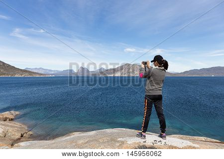 hipster woman on rock beach taking photo with camera for blue sea blue sky and nice mountain.