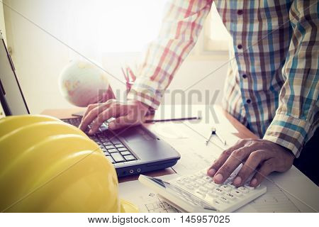 Architect Working On Calculator And Laptop