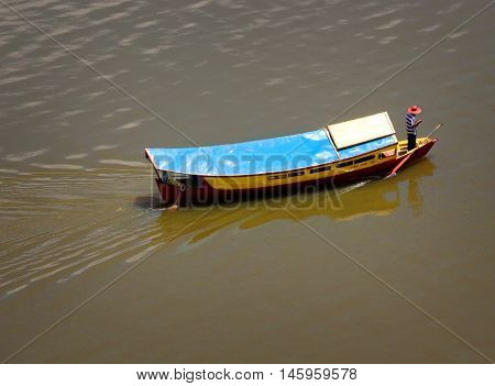 KUCHING, BORNEO, SARAWAK, EAST MALAYSIA - SEPTEMBER 5 2016: A water taxi is navigated by its pilot on the Kuching River in Sarawak, East Malaysia.  The Water taxi in Borneo is a common mode of transportation, which ferries passengers on short inexpensive