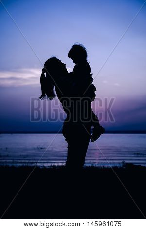 Silhouette side view of mother and child enjoying at riverside. Mother carrying her daughter. Happy family spending time together. Friendly family. Cool colors tone photo effect.