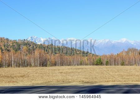 View from the road to the mountains covered with snow