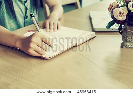 Asian girl hands with pen writing on leather notebook.Beautiful hand holding pen for writing.Vintage tone