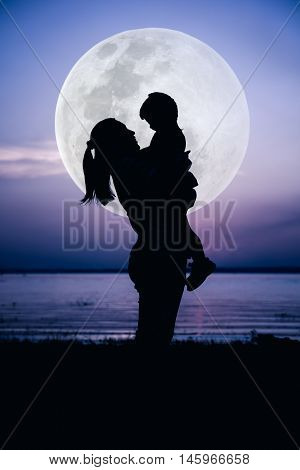 Silhouette side view of mother and child enjoying with large moon. Mother carrying her daughter. Happy family spending time together. Cool colors tone photo effect. The moon were NOT furnished by NASA.