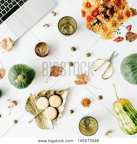 autumn fall flat lay top view home office table desk. workspace with laptop chrysanthemum bouquet pumpkin leaves scissors on white background flat lay top view
