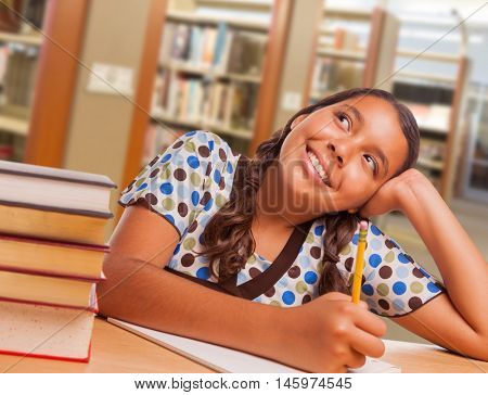 Happy Hispanic Girl Student with Pencil and Books Daydreaming While Studying in Library.