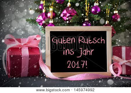 Chalkboard With German Text Guten Rutsch Ins Jahr 2017 Means Happy New Year. Christmas Tree With Rose Quartz Balls, Snowflakes And Bokeh Effect. Gifts Or Presents In The Front Of Cement Background.