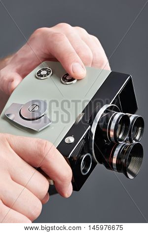 Retro Mechanical Hobbies Movie Camera In Hands Isolated