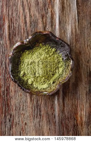 Dry Matcha Tea In A Small Brown Plate. Dark Wood Background. Top