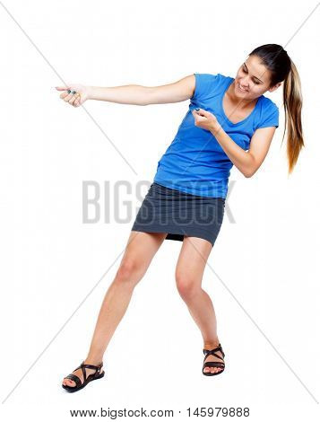 back view of standing girl pulling a rope from the top or cling to something. girl watching. girl in a short skirt and a blue shirt pulling rope.