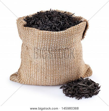 Black tea in burlap bag with heap near isolated on white background. Black tea. Dry leaves of tea in sack isolated on white
