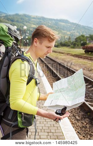 portrait of hiker man with backpack reading map at the train station. Traveler holding map and compass waiting for a train at train station and planing for next trip. Hiking. Tourist at the train station
