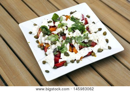 square white plate with caprese salad and capres on wooden table