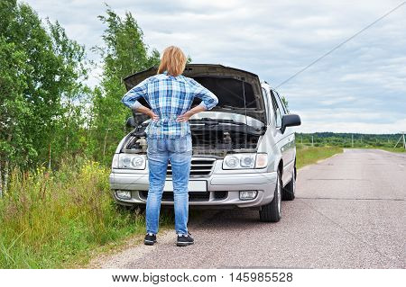 Woman Looking Under Hood Of Broken Car