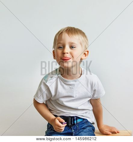 Little Boy Teasing, Showing Tongue And Makes A Face, On White Background, Soft Focus