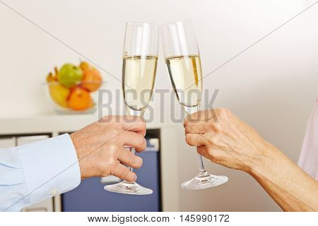 Old hands clinking champagne glasses for celebration