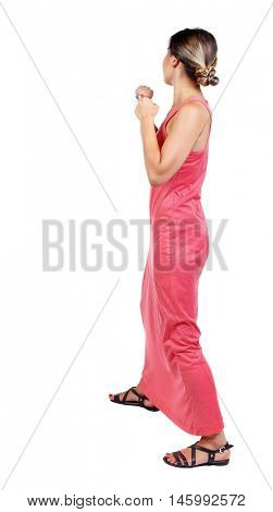 skinny woman funny fights waving his arms and legs. slender woman in a long red dress is standing with clenched fists.